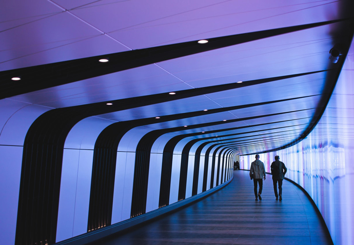 Client and marketing agency team member walking down a corridor in a futuristic office building