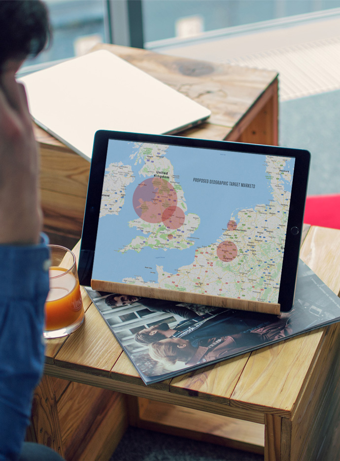 Client reviewing proposed geographic target markets on an iPad during a meeting with their strategic marketing agency